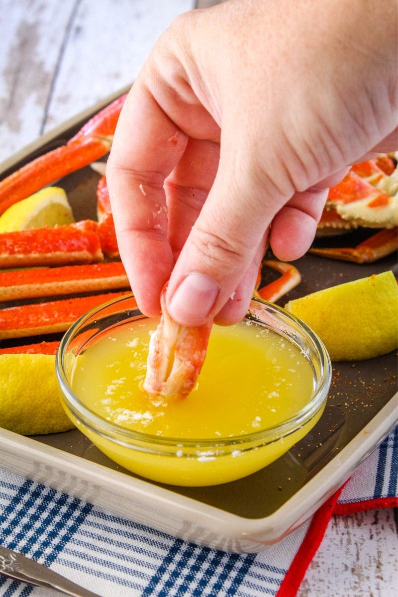 piece of crab meat being dipped into melted butter