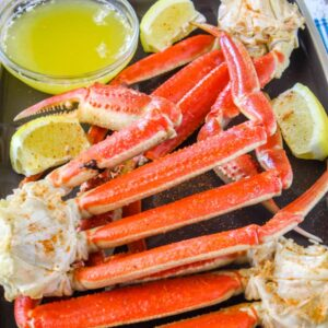 Crab legs with melted butter and lemon wedges.