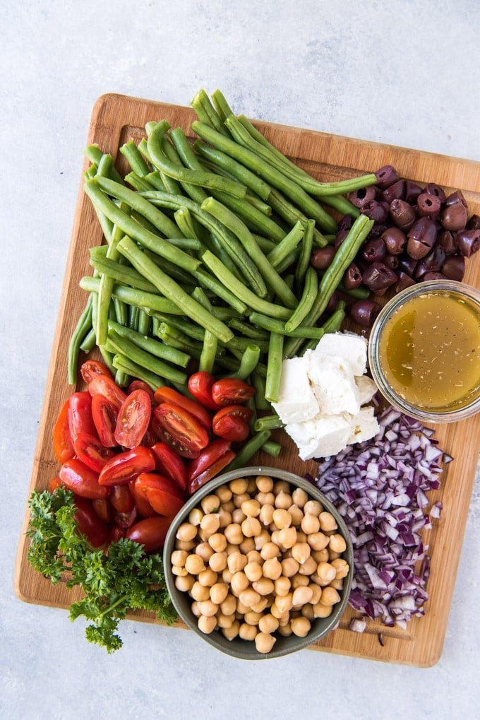 A wooden cutting board with green beans, olives, tomatoes, chickpeas, parsley, onions, feta cheese and a bowl of dressing.