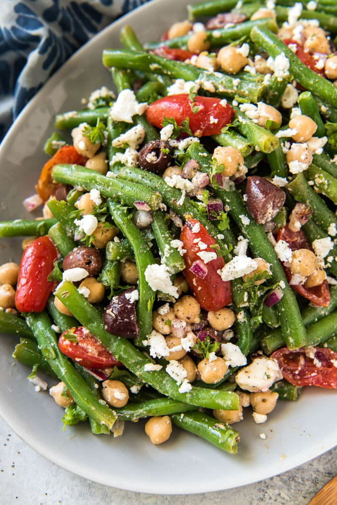 A close up overhead image of a white plate filled with green bean, tomatoes, olives, chickpeas and feta cheese. A blue and white napkin sits off to the sides.