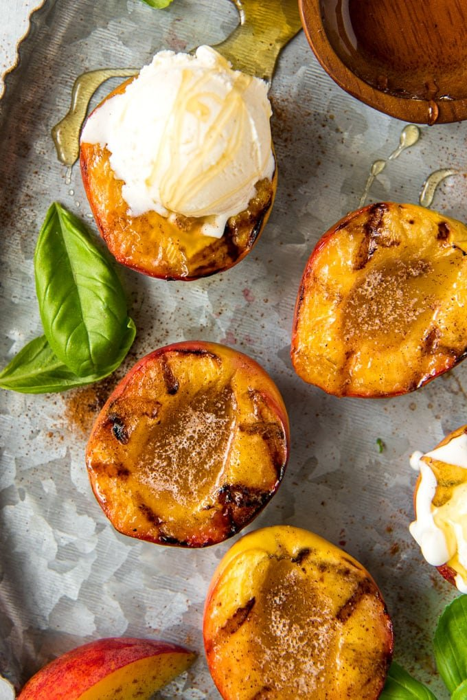 4 peach halves with grill marks and melted butter. One has ice cream in it and there is honey drizzled all around