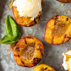 A close up of grilled peaches with vanilla ice cream.