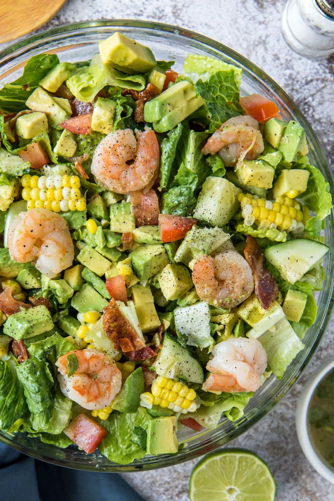 a clear glass bowl with lettuce, avocado, shrimp and corn and tomatoes. A lime half.