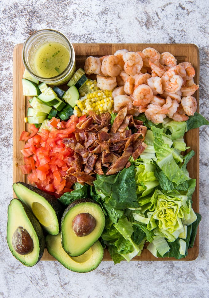 a wood cutting board, 4 avocado halves, chopped lettuce, diced tomatoes, chopped cucumber, shrimp, bacon and corn. a clear glass jar with yellow dressing.