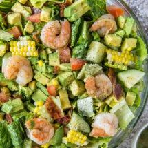 A bowl of salad, with shrimp, corn, and avocado.