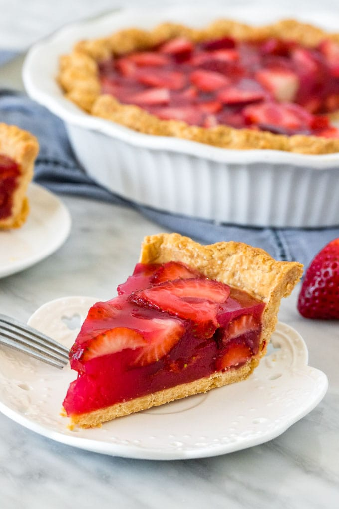 Slice of strawberry jello pie on a white plate. a whole strawberry pie in a white dish. A blue napkin.