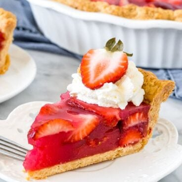 Slice of strawberry pie with whipped cream and a strawberry on top.