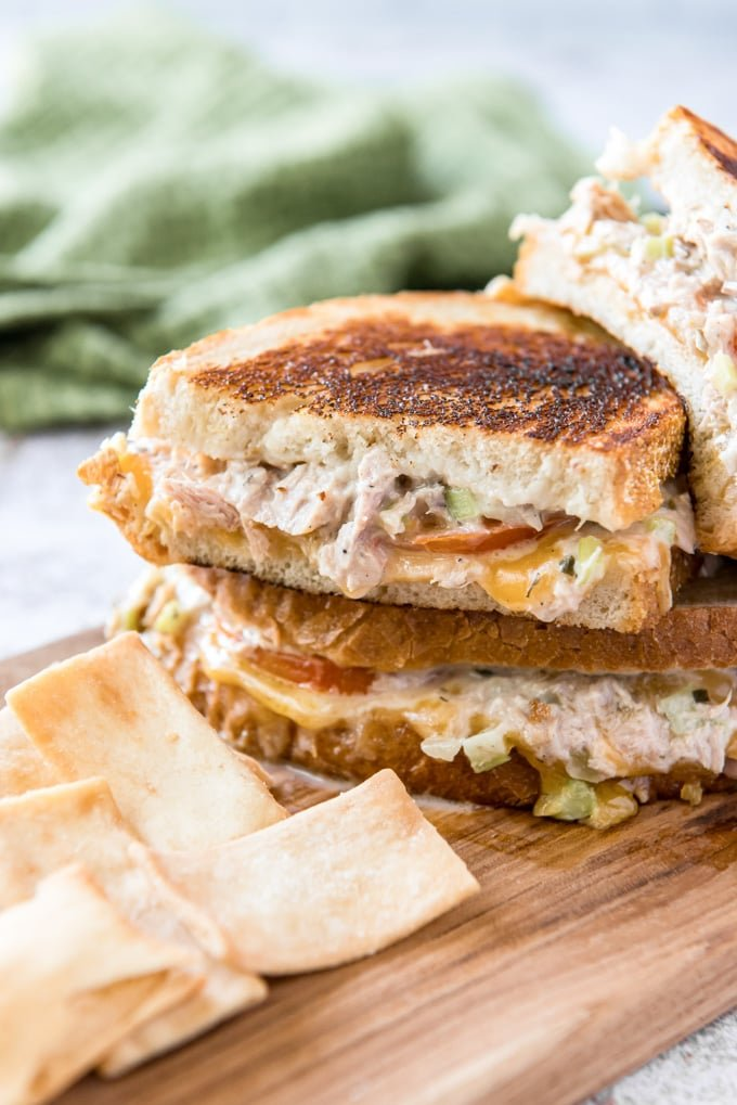 A Tuna Melt is a classic hot grilled sandwich, with flavorful tuna fish salad, fresh sliced tomatoes and melted cheddar cheese all served on toasted bread.