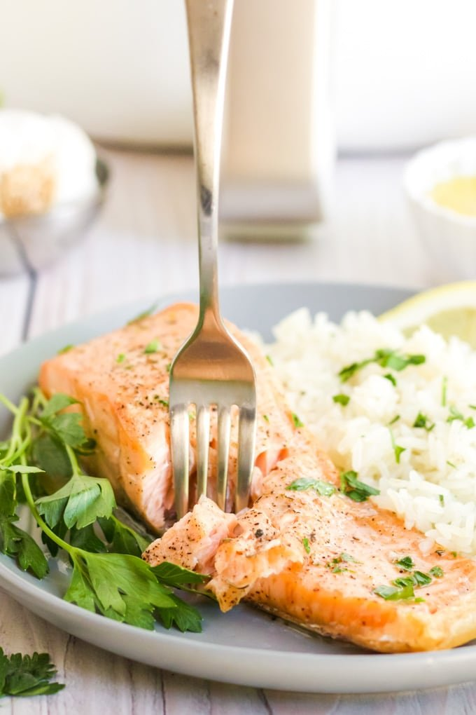 Air fryer salmon with a fork in it with rice and herbs surrounding it on the plate.