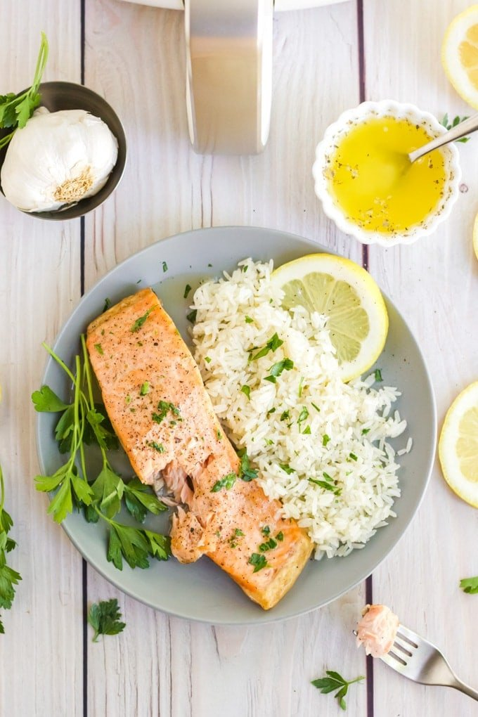 Overhead image of air fryer salmon next to a bed of white rice and garnished with fresh herbs