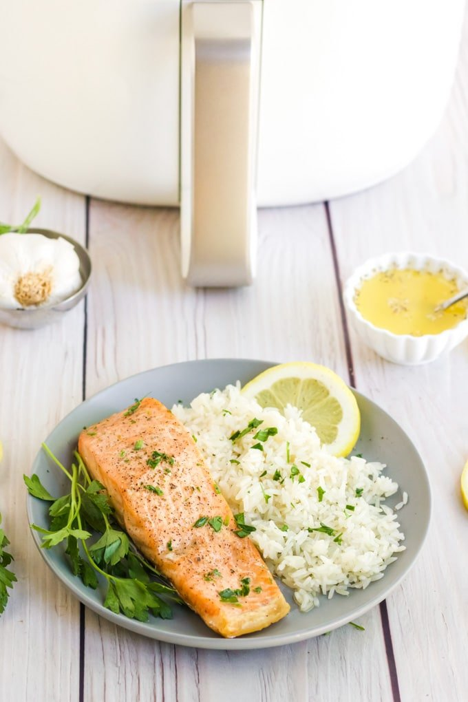 Air Fryer Salmon on a grey plate with white rice and a white air fryer in the background.