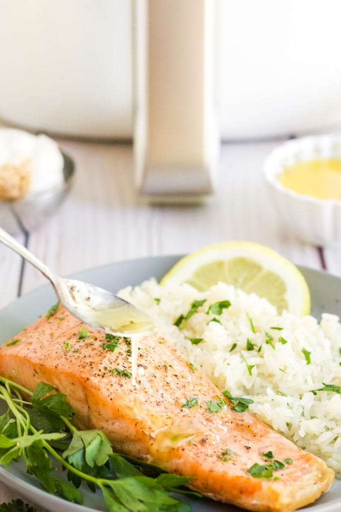 Lemon Garlic Herb Butter being spooned on to air fryer salmon