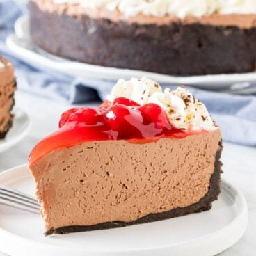A piece of chocolate cheesecake cake on a plate, with cherry topping and whipped cream.