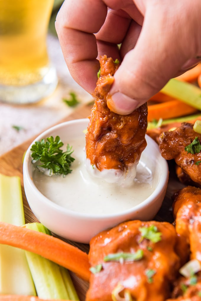 a hand holding a boneless buffalo chicken wings dipped in ranch dressing. carrots and celery sticks, a wood background, a glass of beer