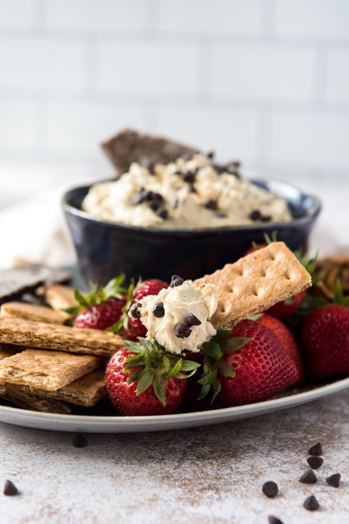 a white plate, scattered mini chocolate chips, graham crackers, strawberries cookie dough dip in a blue bowl.