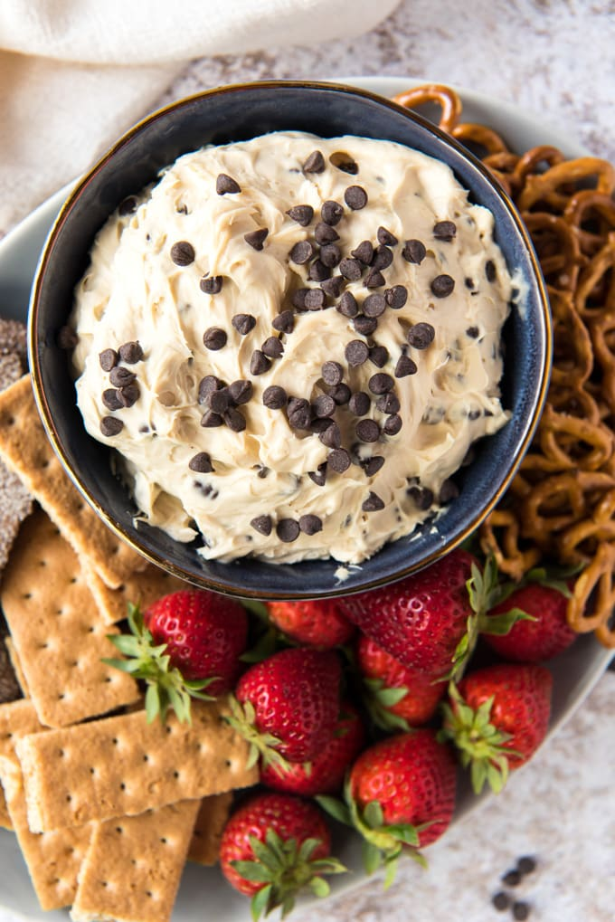 a white plate with graham crackers, strawberries, pretzels, a small blue bowl with cookie dough dip