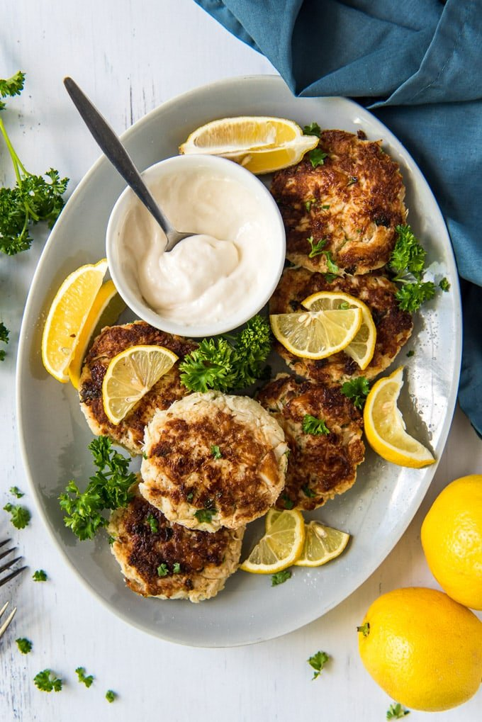 a large white platter, crab cakes, lemon slices, a bowl with tartar sauce and a spoon, a blue napkin, parsley
