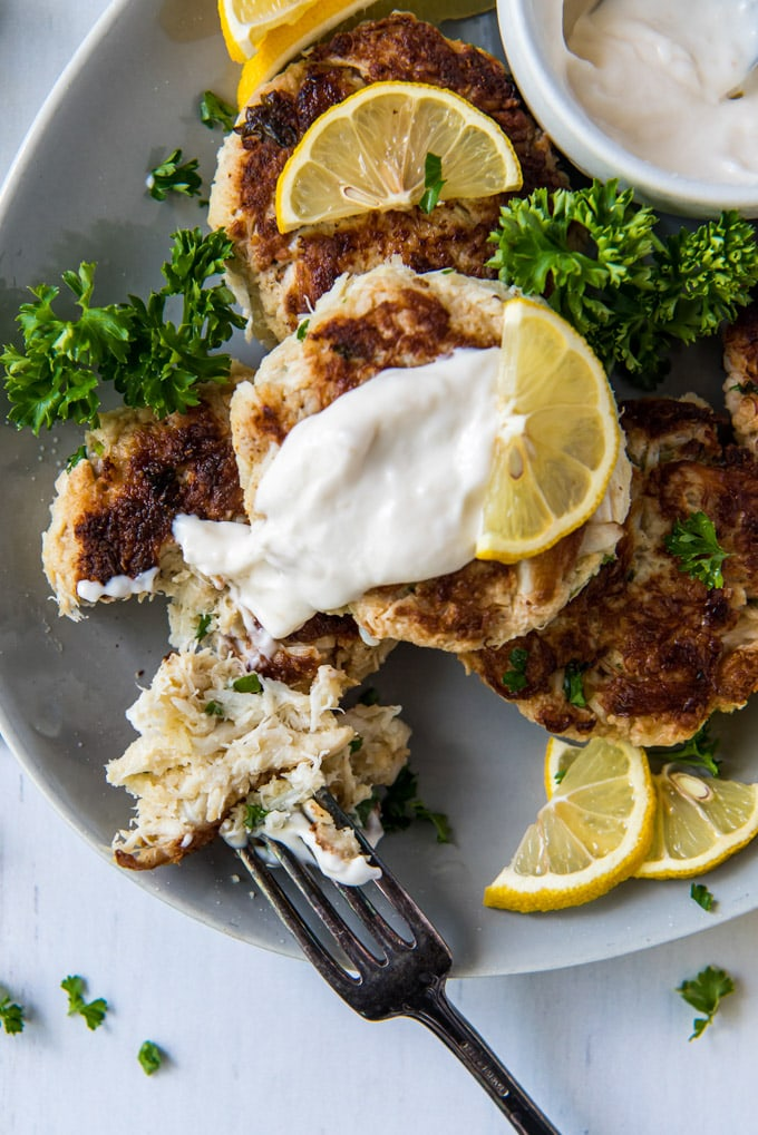 a white plate, a stack of crab cakes, lemons, tartar sauce, a crab cake pulled apart to show the interior, parsley