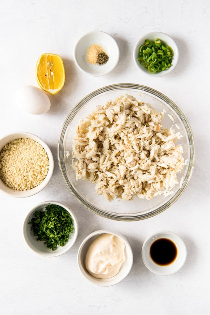 7 small white bowls with ingredients for making crab cakes. An egg, a lemon and a large clear glass bowl full of crab meat.