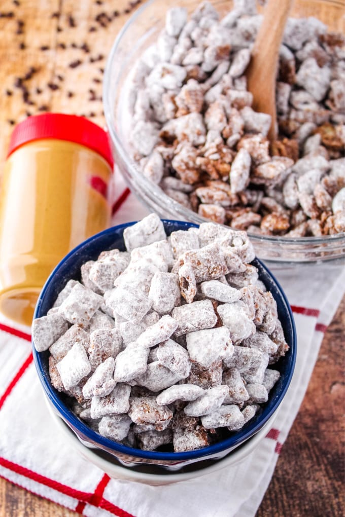 muddy buddies in a bowl with a jar of peanut butter and chocolate chips around it