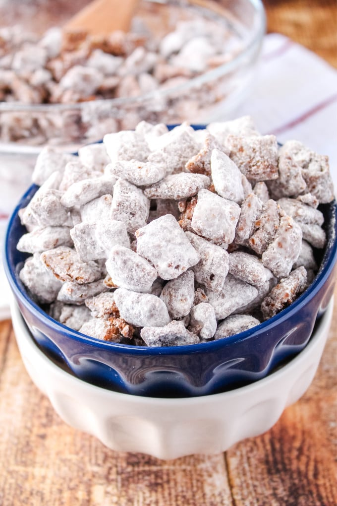 muddy buddies in a small bowl with a bigger bowl and spoon behind