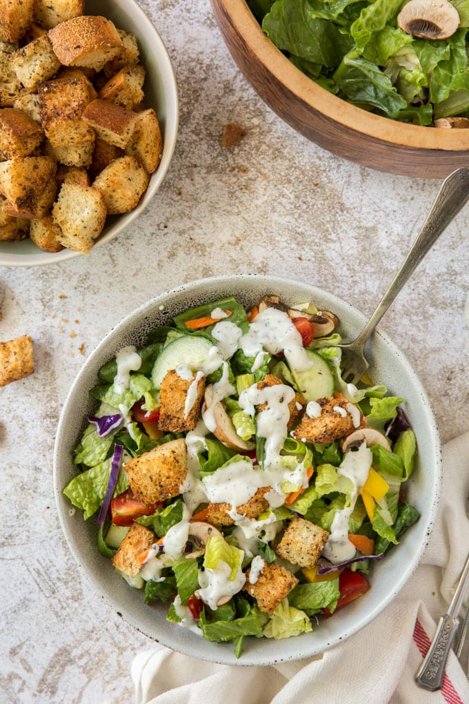 a white bow with salad, ranch dressing and a fork, a white bowl with croutons, a wood bowl with salad
