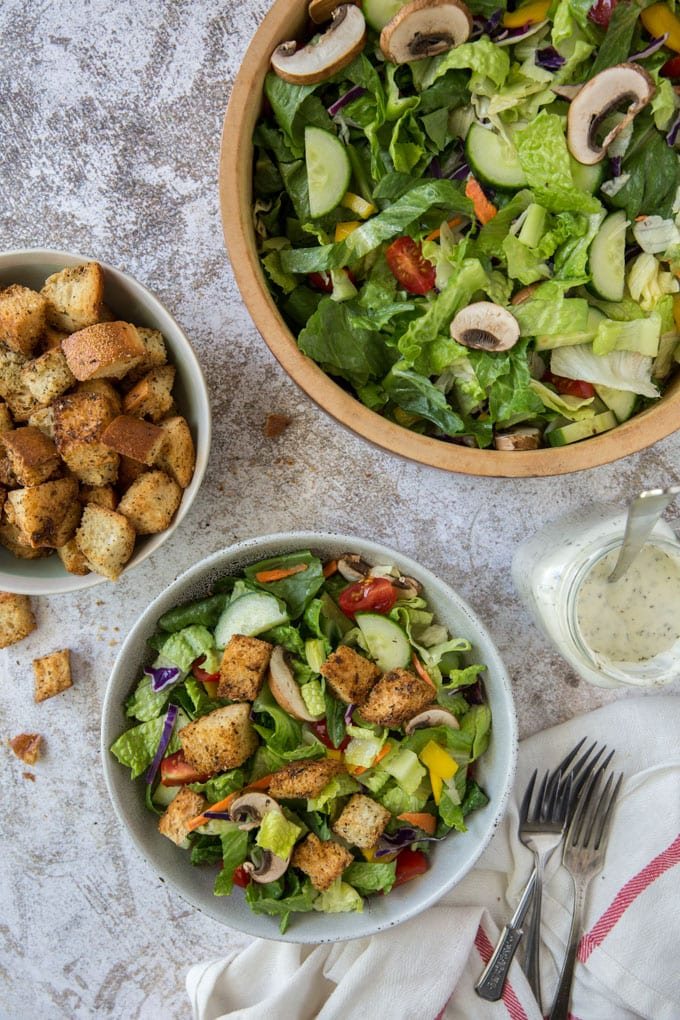 a white bowl with salad, a white bowl with croutons, forks, a white towel with a red stripe and a wooden bowl with salad and veggies, a mason jar with ranch dressing and a spoon.