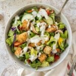 A bowl of salad with ranch dressing.