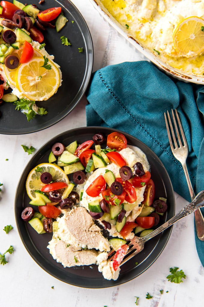 two black plates with chicken, cucumbers, olives, tomatoes, a blue napkin, a fork a whilte casserole dish with chicken and cheese in it.