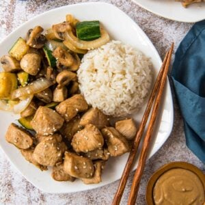 A plate of chicken, vegetables, and white rice, with chopsticks.
