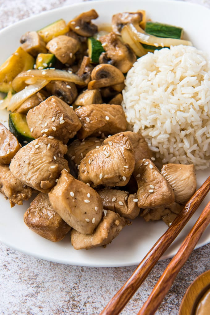 white plate, chopsticks, white rice, chicken and vegetables