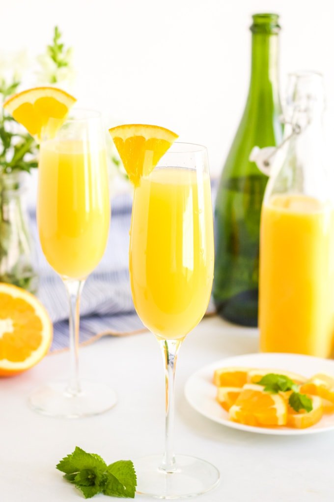 A traditional mimosa with oranges, orange juice and sparkling wine in the background.