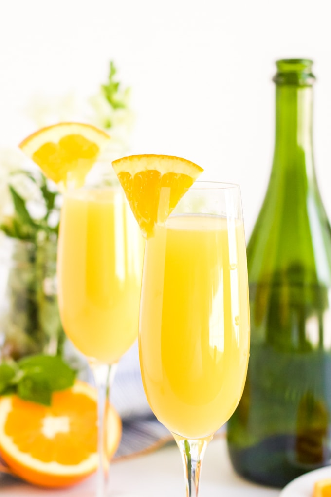 Two glasses of traditional orange juice cocktails with a sparkling wine bottle in the background.