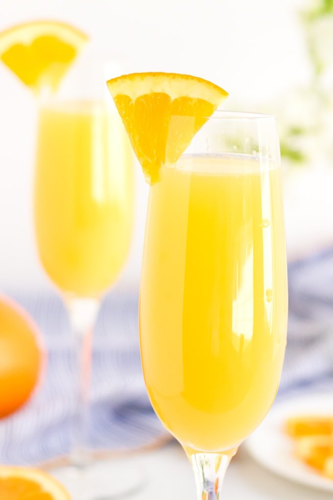 Champagne flutes with orange juice and an orange slice on the rim. A blue napkin and oranges in the background.