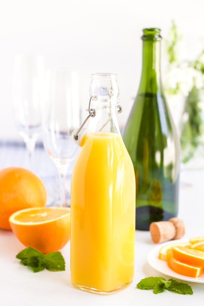 Ingredients for a classic mimosa. Orange juice, oranges and sparkling wine.