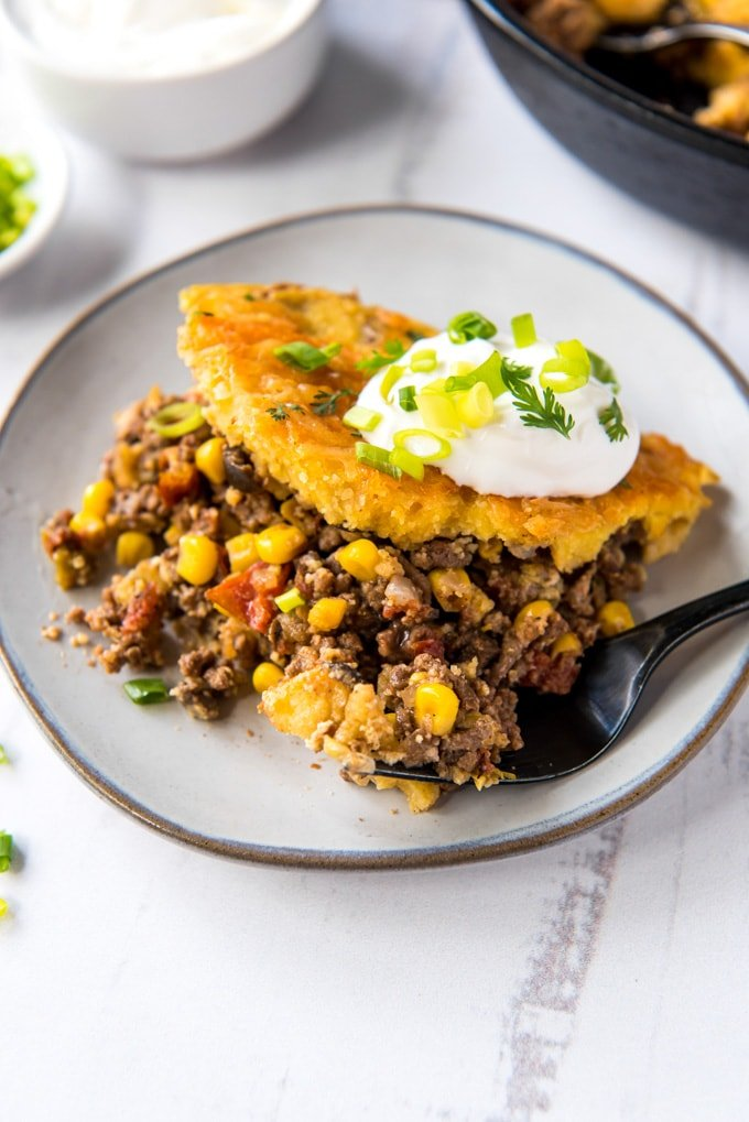 white plate with ground beef anc corn, cornbread topping and sour crea. A fork, a white dish