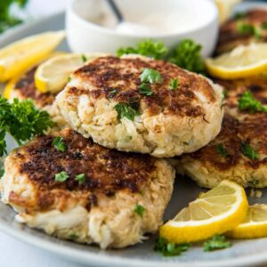 A plate of crab cakes, with lemon wedges.