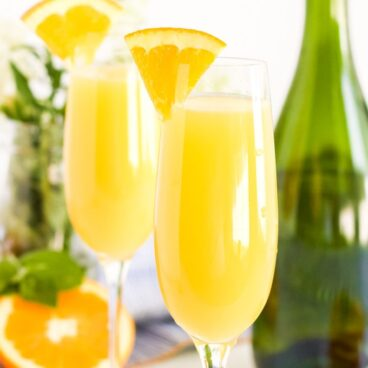 square image of 2 champagne glasses with orange juice mimosas and a green champagn bottle, an orange slice and some mint.