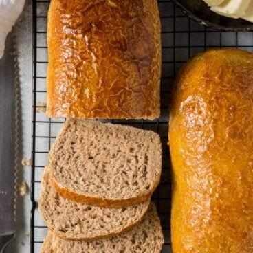 two loaves of whole wheat bread on a cooling rack. One loaf sliced into a few pieces.
