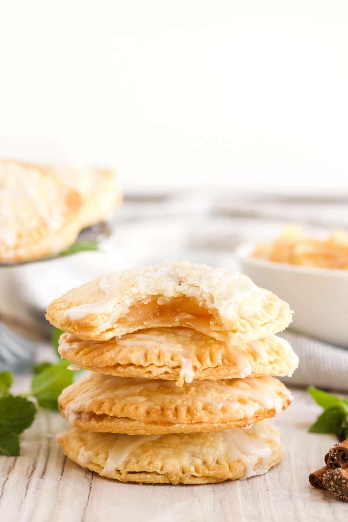 Air Fryer Apple Hand Pies stacked up with apple pie filling showing in the top pie.