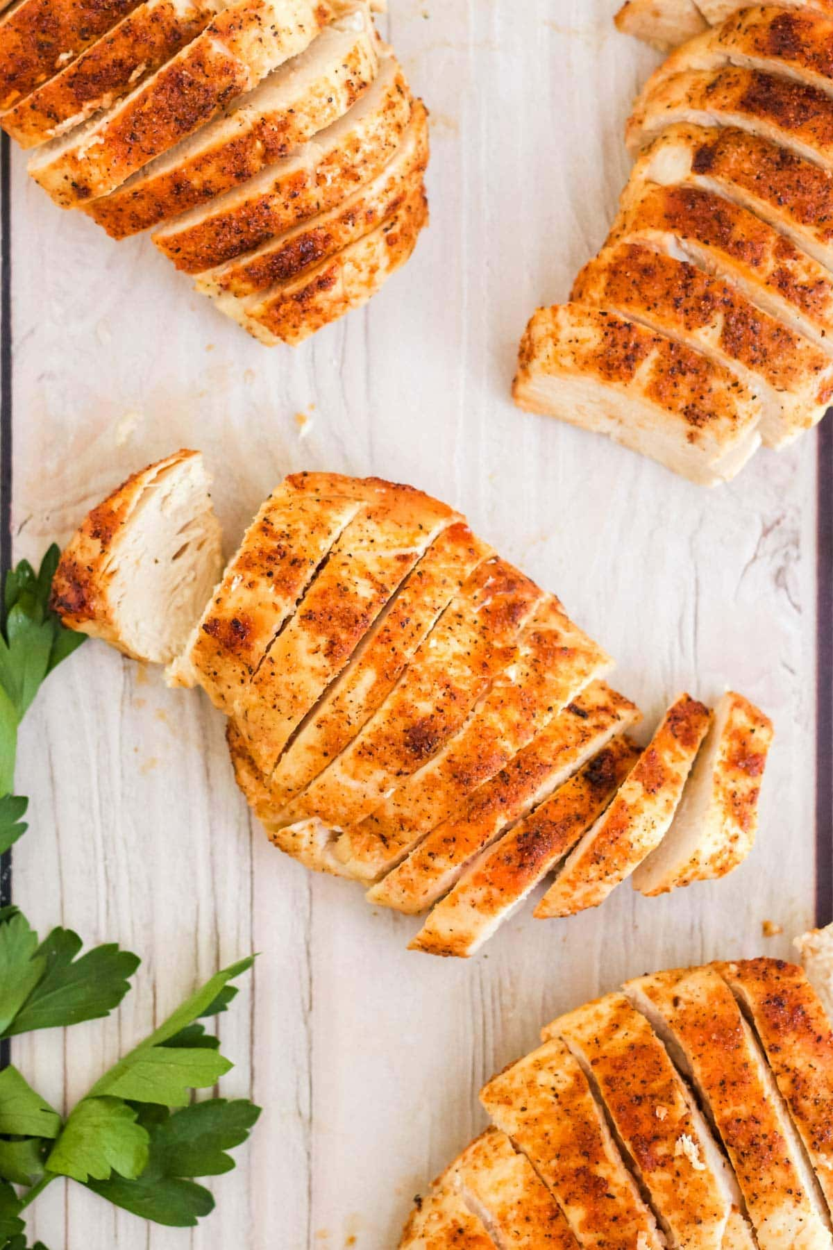 chicken breasts, sliced, on a white wood background, parsley