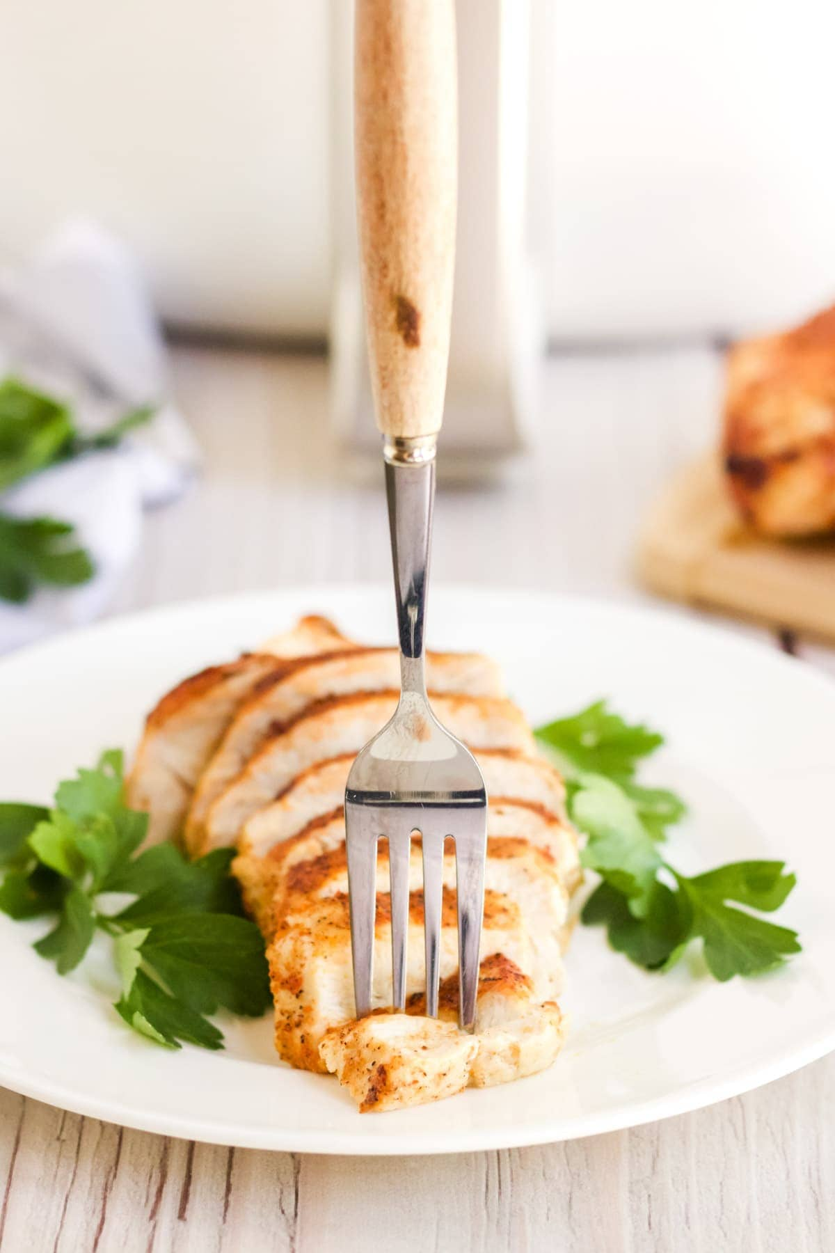 sliced chicken breast on a whilte plate with parsley and a fork