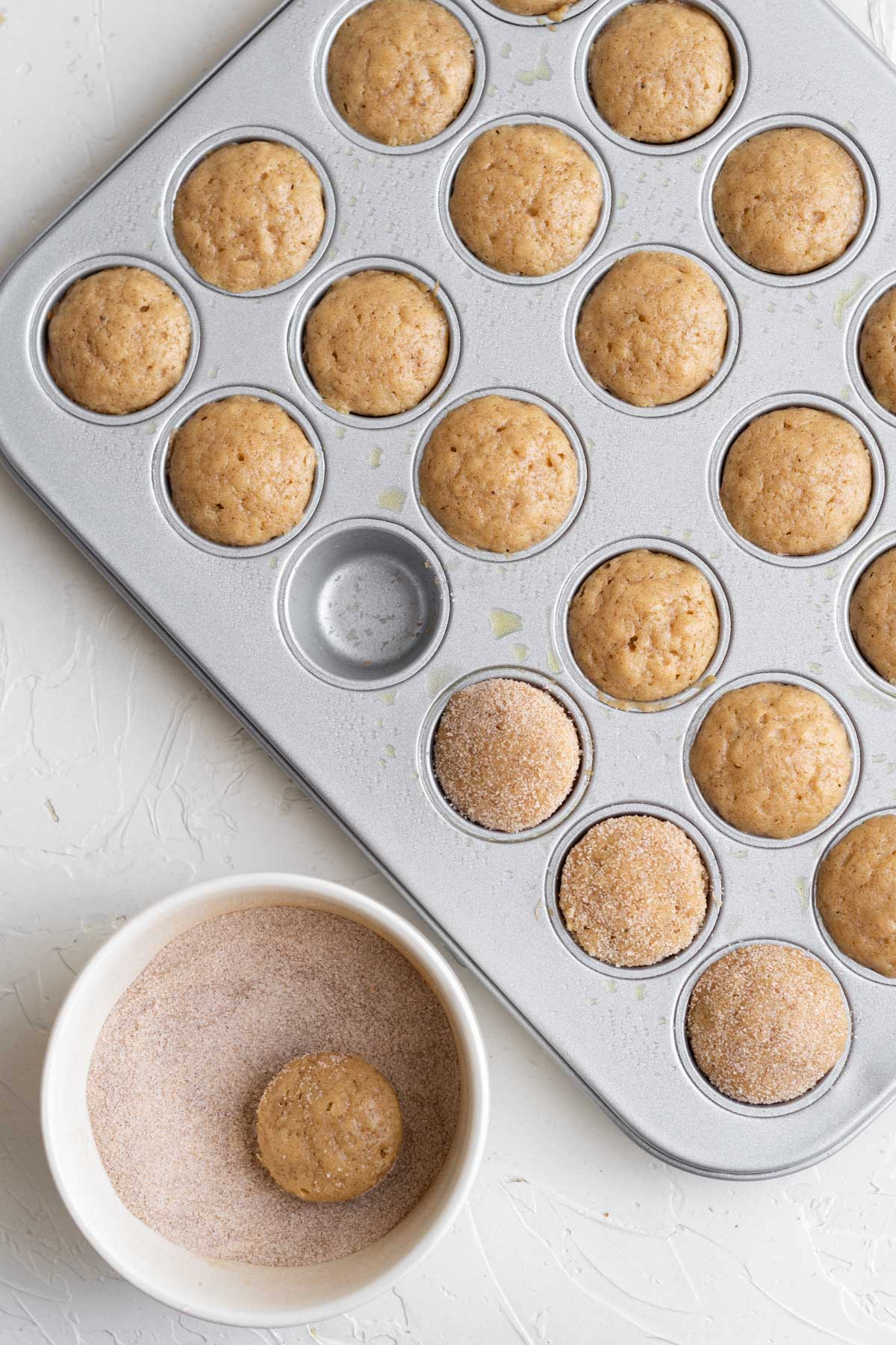 apple cider donut holes in a mini muffin pan, one sits in a white dish of sugar and cinnamon