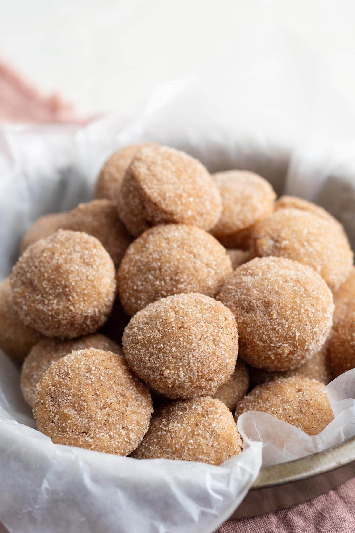 donut holes in a basket with a white towel, coated in cinnamon sugar