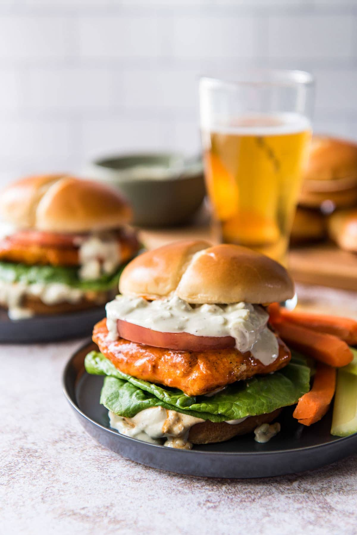 two black plates, 2 buffalo chicken sandwiches on buns with creamy sauce, lettuce and tomato, a beer, carrot and celery sticks