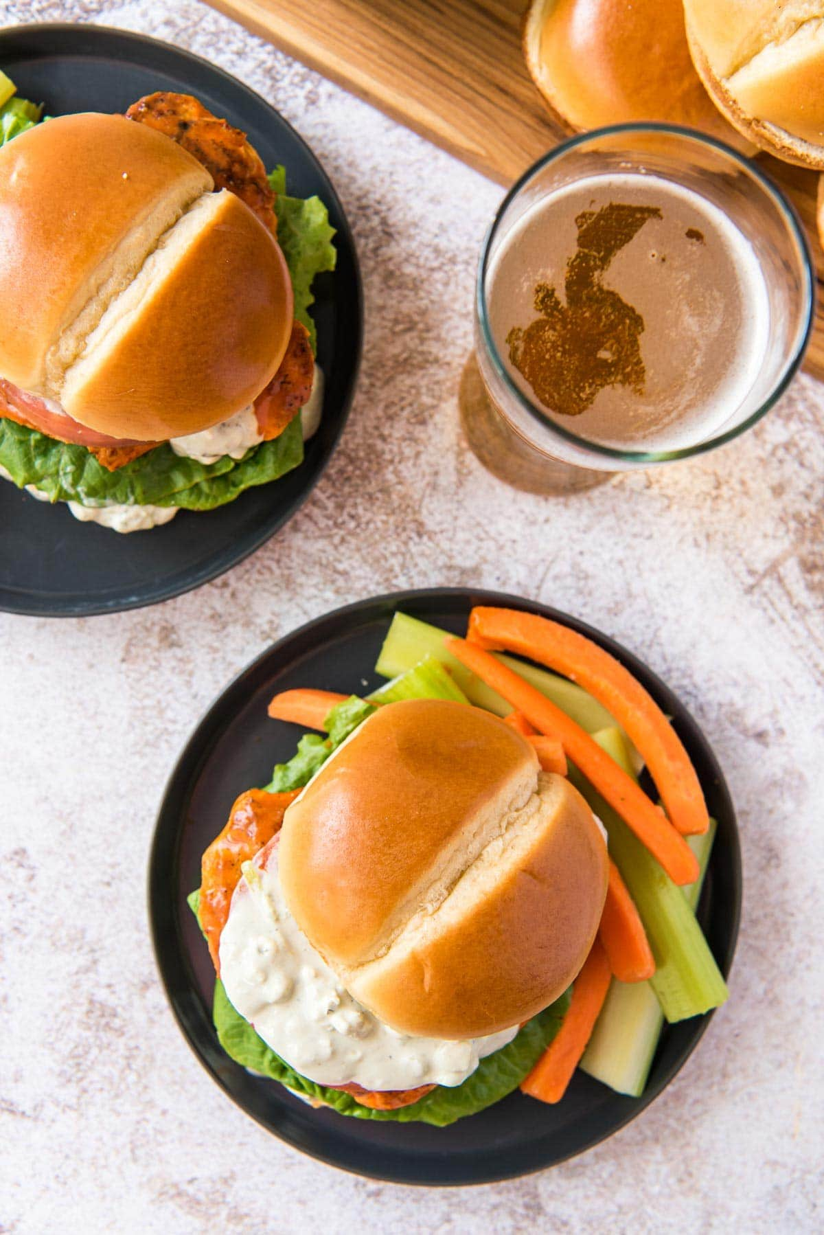 Overhead shot of 2 buffalo chicken sandwiches on black plates, a beer, brioche buns on a wood cutting board