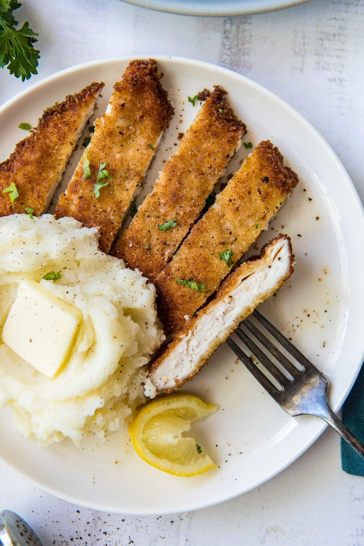 mashed potatoes and sliced breaded chicken on a white plate with a fork