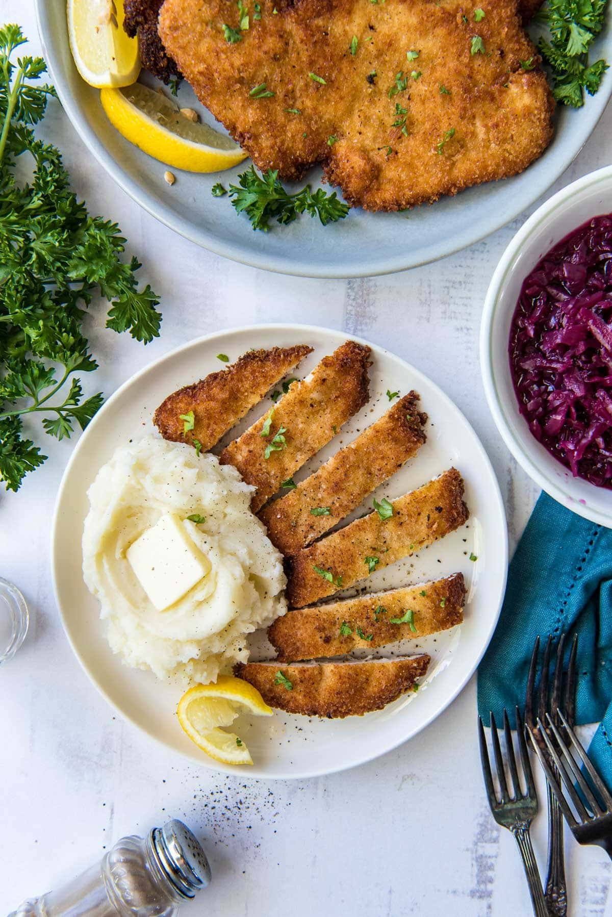 3 white plates, red cabbage, mashed potatoes, fried chicken cutlets, blue napkin, forks, parelsy