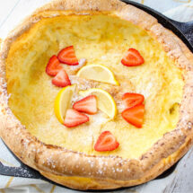 square image of german pancake topped with powdered sugar lemons and strawberries