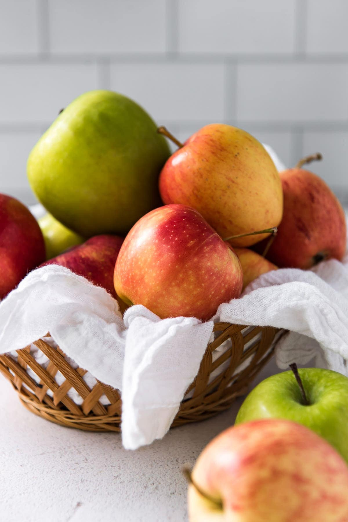 basket with white napkin, green and red apples